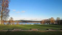 Vår exceptionellt vackert belägna driving range med Rådasjön i bakgrunden